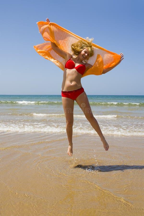Funcionamentos da menina na praia fotografia de stock