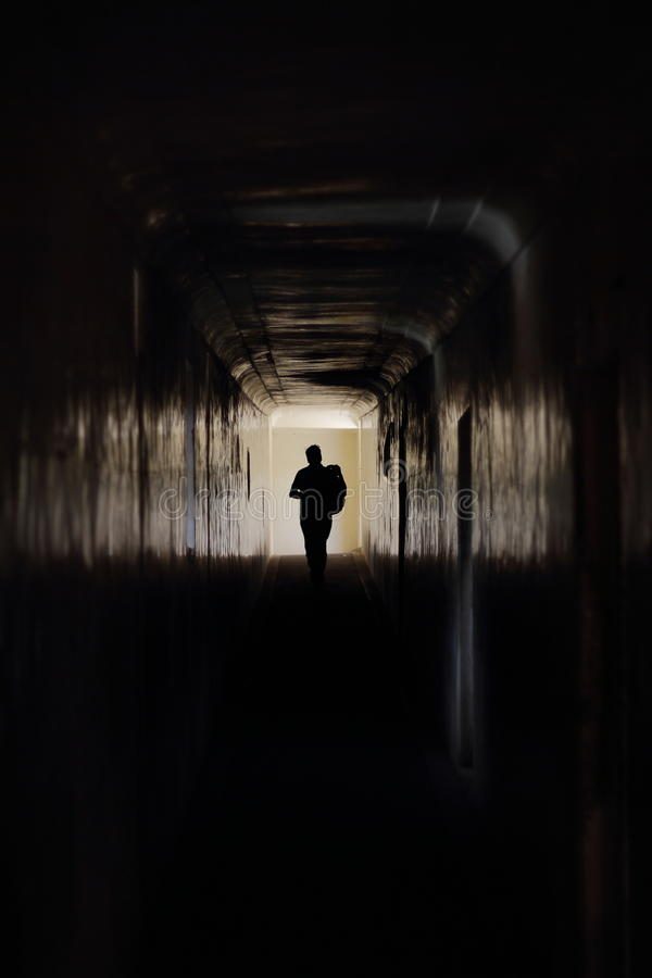 Funcionamentos do homem ao longo de um corredor escuro imagens de stock royalty free