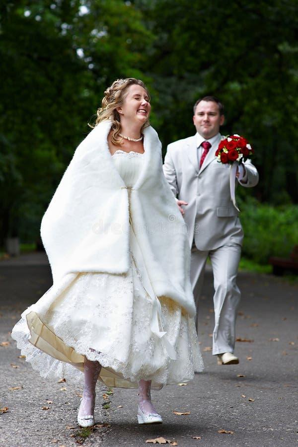 Funcionamentos do noivo após a noiva foto de stock