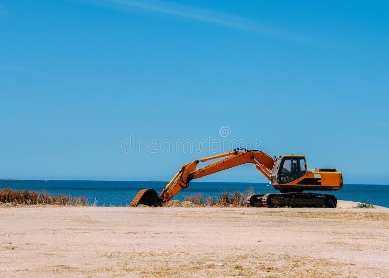 Funcionamiento amarillo de la niveladora en una playa con el espacio de la copia imágenes de archivo libres de regalías