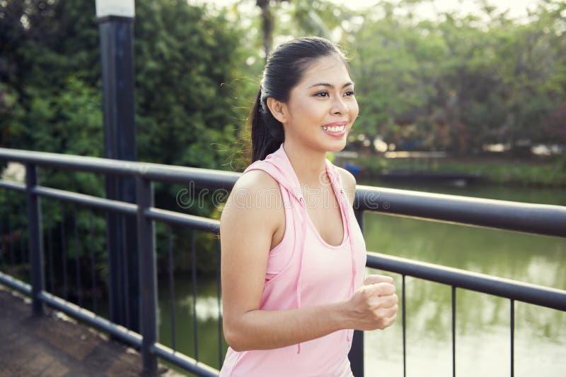 Funcionamiento asiático feliz de la mujer del atleta imagen de archivo libre de regalías