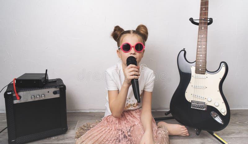 Funcionamiento casero: Una chica joven se sienta en el piso que canta con un micrófono Cerca coloca el equipo de la música fotografía de archivo