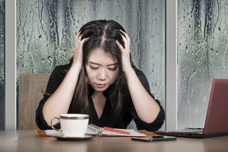 Funcionamiento chino asiático triste y deprimido hermoso joven de la mujer de negocios agotado y frustrado en el escritorio del o fotos de archivo libres de regalías