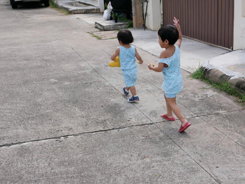 Funcionamiento correcto del pequeño bebé asiático después de su hermana del bebé y goce acompañando a su hermana mientras que apr fotografía de archivo