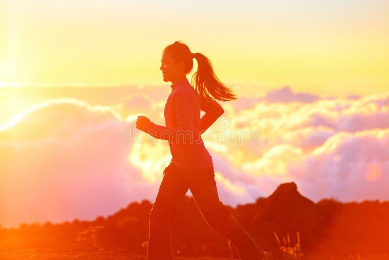 Funcionamiento - corredor de la mujer que activa en la puesta del sol imagen de archivo