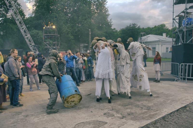 Funcionamiento de la calle de la tarde Para mujer en los zancos con caretas antigás y un hombre con un barril en el humo Película foto de archivo