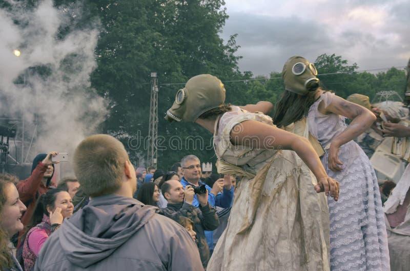 Funcionamiento de la calle de la tarde Para mujer en los zancos con las caretas antigás y los libros en sus cuellos en humo fotografía de archivo