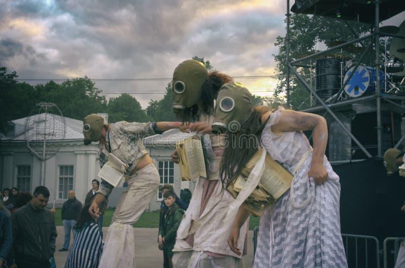 Funcionamiento de la calle de la tarde Para mujer en los zancos con las caretas antigás y los libros en sus cuellos en humo Pelíc imagen de archivo