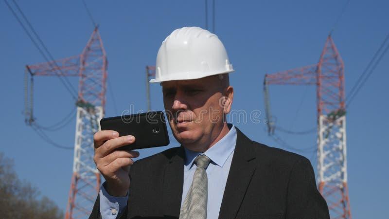 Funcionamiento de la energía en texto enérgico de la industria usando móvil en actividad del mantenimiento fotografía de archivo libre de regalías