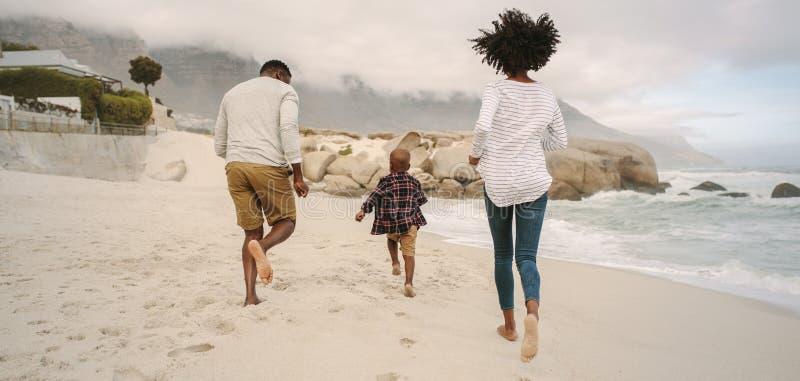 Funcionamiento de la familia en la playa imagen de archivo libre de regalías