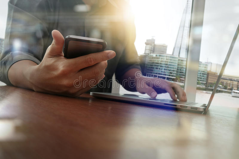Funcionamiento de la mano del diseñador y teléfono y ordenador portátil elegantes imagen de archivo