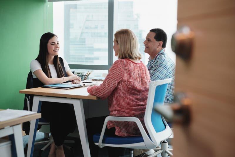 Funcionamiento de la mujer como consejero de inversión que habla con los clientes en oficina fotografía de archivo libre de regalías