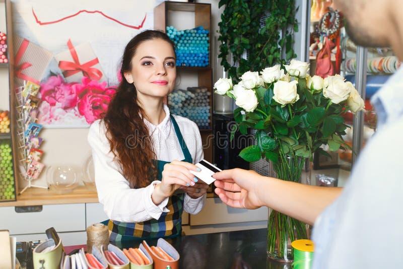 Funcionamiento de la mujer joven como florista que da la tarjeta de crédito al cliente fotos de archivo libres de regalías