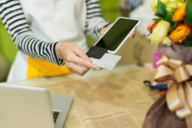 Funcionamiento de la mujer joven como pago del florista usando tarjeta de crédito al cust fotos de archivo libres de regalías
