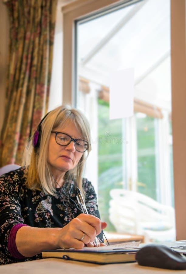 Funcionamiento de la mujer de la observación webinar en su ordenador portátil, auriculares que llevan del hogar fotografía de archivo libre de regalías