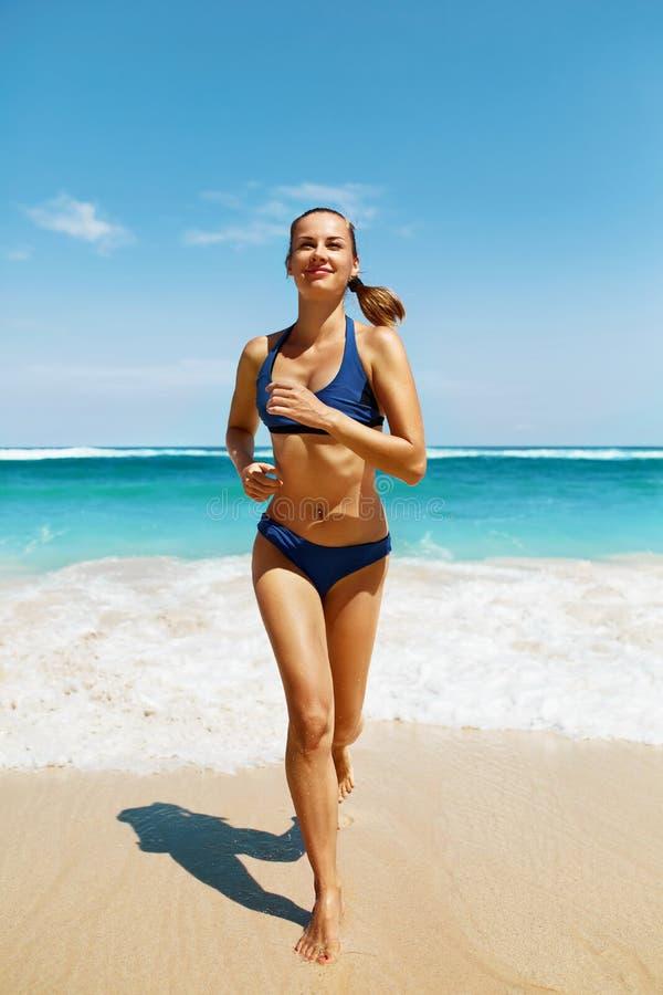Funcionamiento de la playa Mujer de la aptitud en el bikini que corre en verano imagenes de archivo