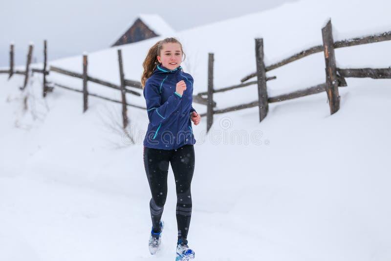Funcionamiento del adolescente en rastro de montaña del invierno foto de archivo