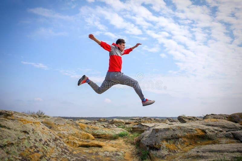 Funcionamiento del deportista, saltando sobre rocas foto de archivo libre de regalías