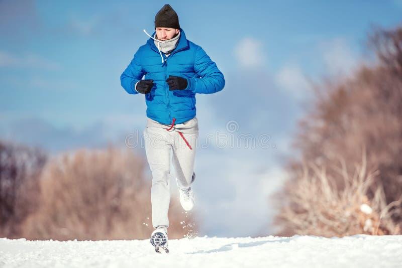 Funcionamiento del hombre de la aptitud al aire libre en nieve en un día de invierno frío imagen de archivo