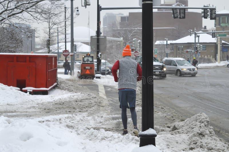 Funcionamiento del hombre después de la tormenta de la nieve imágenes de archivo libres de regalías