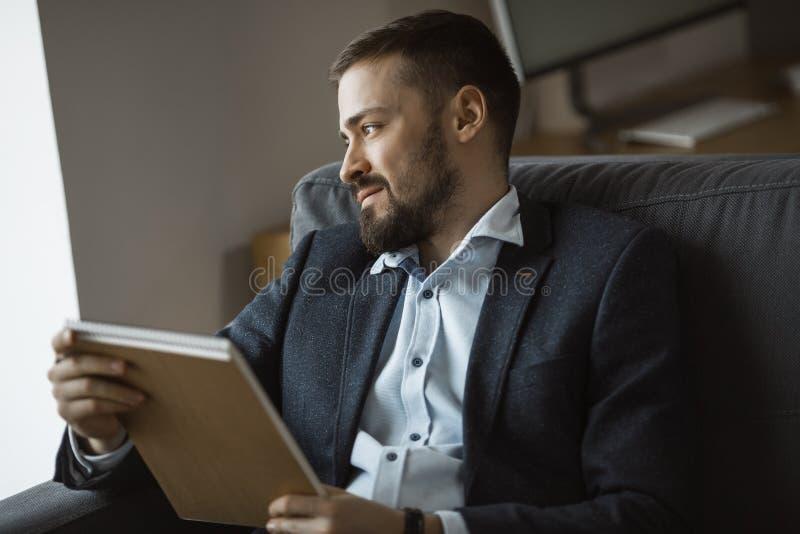 Funcionamiento del hombre en la oficina que hace notas foto de archivo