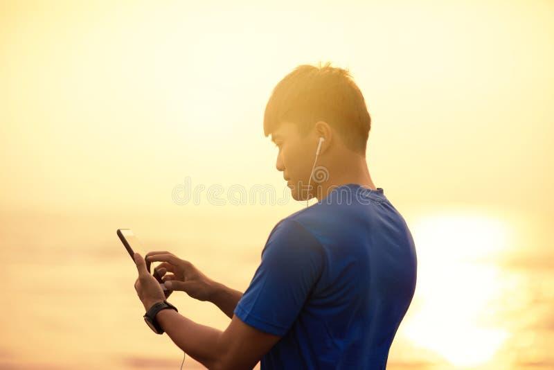 Funcionamiento del hombre en la playa y comprobación del teléfono elegante de Rate Monitor On del corazón fotos de archivo libres de regalías