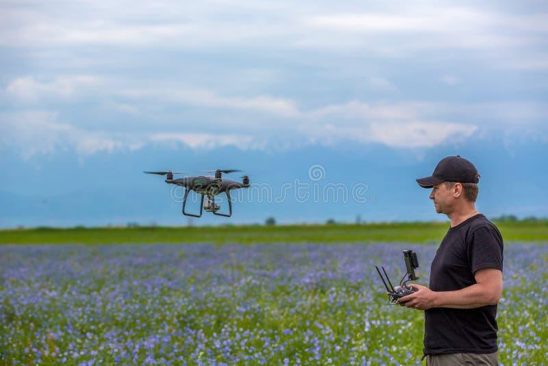Funcionamiento del hombre del quadrocopter del abejón del vuelo en el campo verde imágenes de archivo libres de regalías
