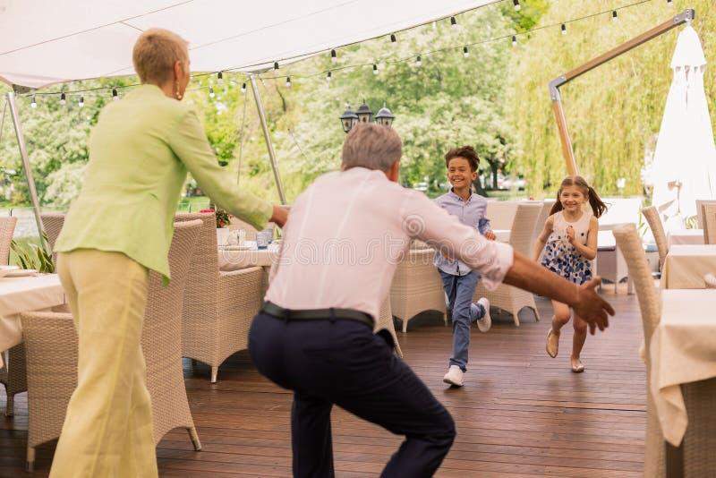 Funcionamiento del muchacho y de la muchacha a los abuelos que pasan fin de semana con ellos fotografía de archivo libre de regalías