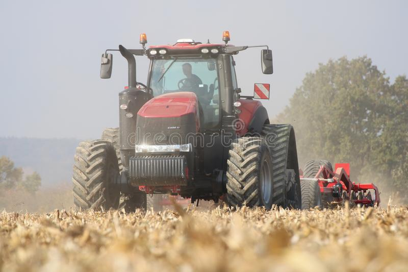 Funcionamiento del tractor en un campo de maíz en la república de checo imagen de archivo libre de regalías