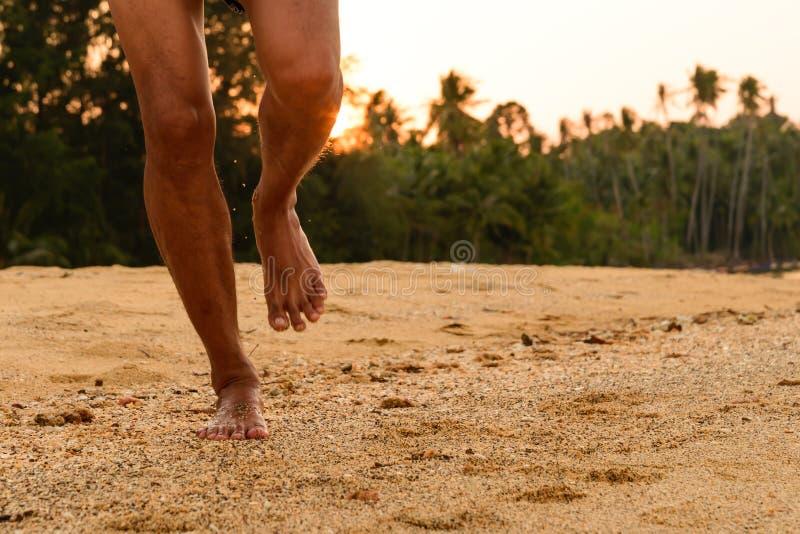 Funcionamiento descalzo en la playa en la puesta del sol foto de archivo