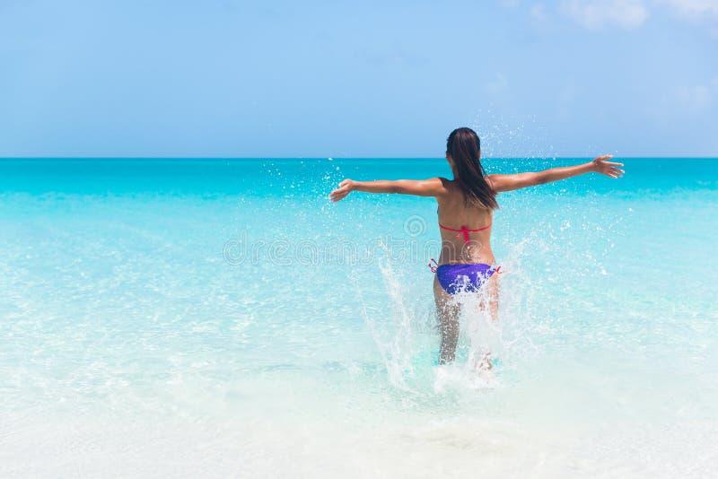 Funcionamiento feliz de la mujer de las vacaciones de verano en playa del agua fotografía de archivo