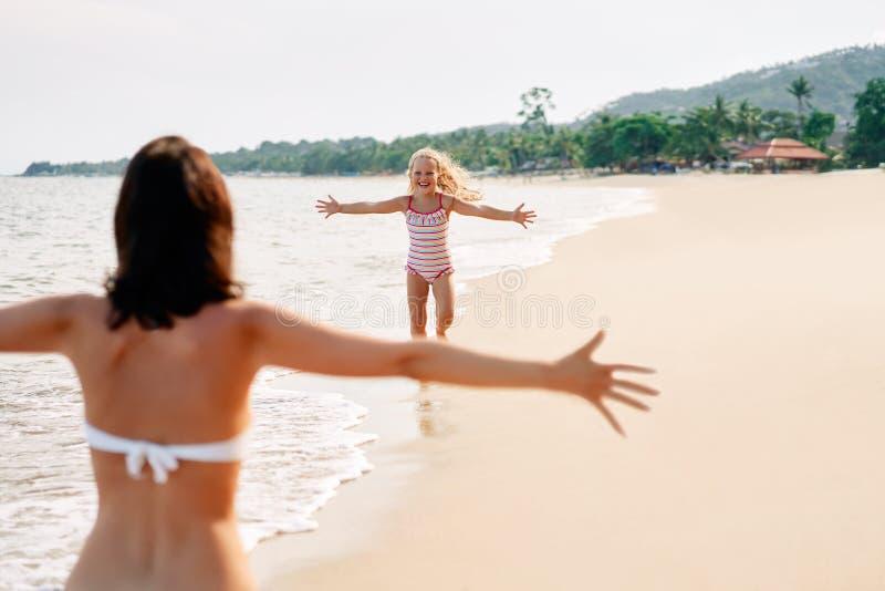 Funcionamiento feliz de la niña a su madre para los abrazos en la playa tropical foto de archivo libre de regalías