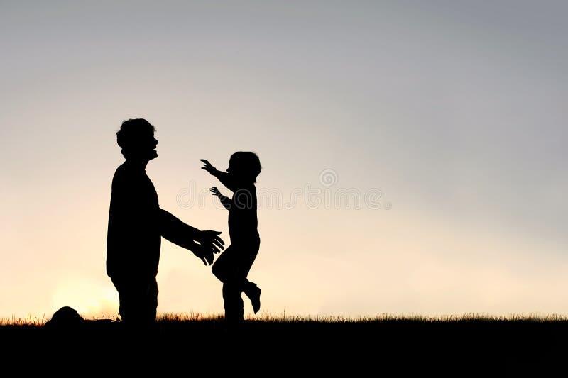 Funcionamiento feliz del niño joven para saludar la silueta del papá foto de archivo libre de regalías