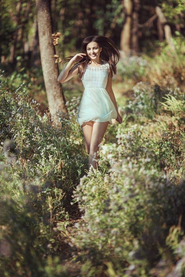 Funcionamiento feliz hermoso de la mujer joven en medow de la flor en bosque fotos de archivo