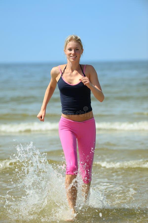 Funcionamiento femenino hermoso en la playa fotografía de archivo libre de regalías