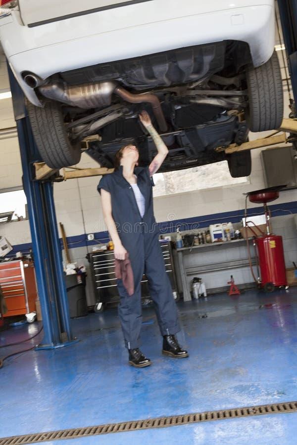 Funcionamiento femenino joven del mecánico mientras que se coloca debajo del coche levantado en taller imágenes de archivo libres de regalías