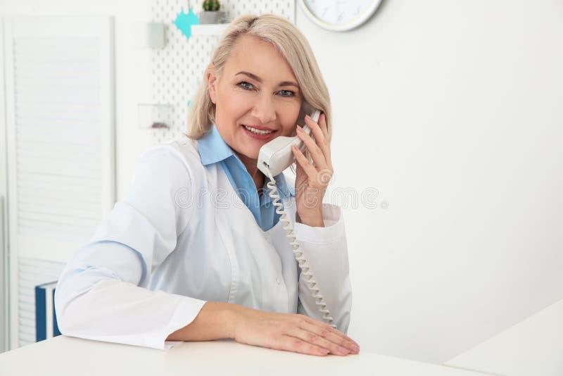 Funcionamiento femenino mayor del recepcionista fotos de archivo