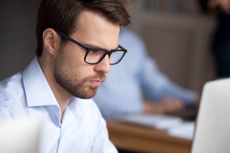 Funcionamiento joven del hombre de negocios del retrato ascendente cercano que mira en la pantalla de ordenador fotografía de archivo libre de regalías