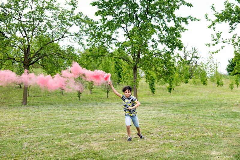 Funcionamiento joven del muchacho que arrastra una llamarada rosada del humo fotos de archivo libres de regalías