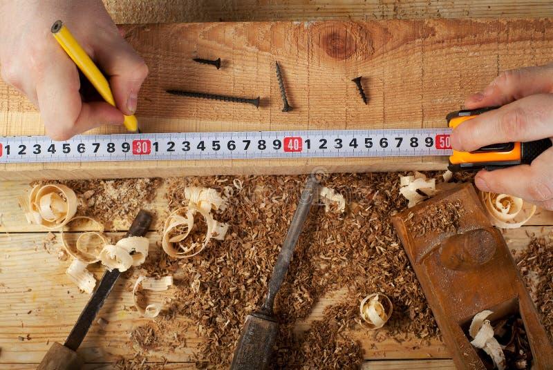 Funcionamiento, martillo, metro y destornillador del carpintero en fondo de la construcción imagen de archivo libre de regalías