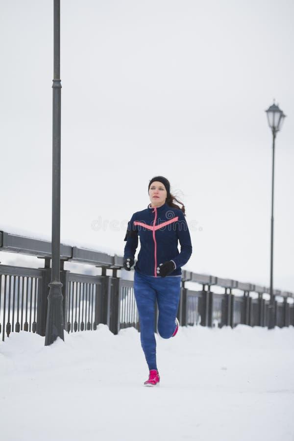 Funcionamiento modelo de la aptitud de la mujer joven en el parque del invierno de la nieve, zapatillas de deporte rosadas foto de archivo libre de regalías