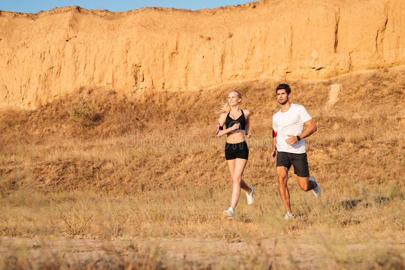 Funcionamiento modelo femenino atlético de la aptitud del corredor y del varón junto imagen de archivo