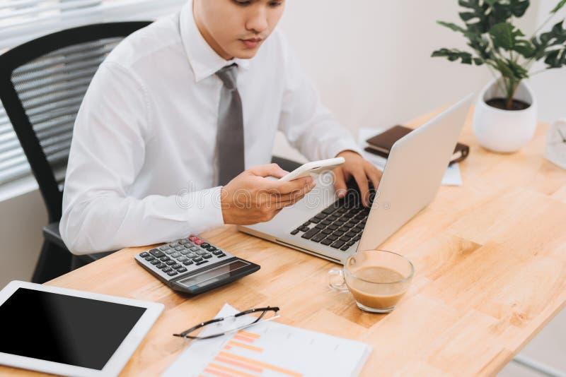 Funcionamiento ocupado del hombre de negocios en el ordenador portátil y consumir el teléfono elegante móvil en la oficina modern imagen de archivo