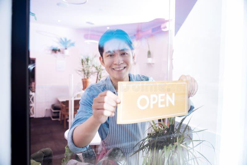 Funcionamiento oscuro-cabelludo sonriente del estudiante como barista por la mañana imagenes de archivo