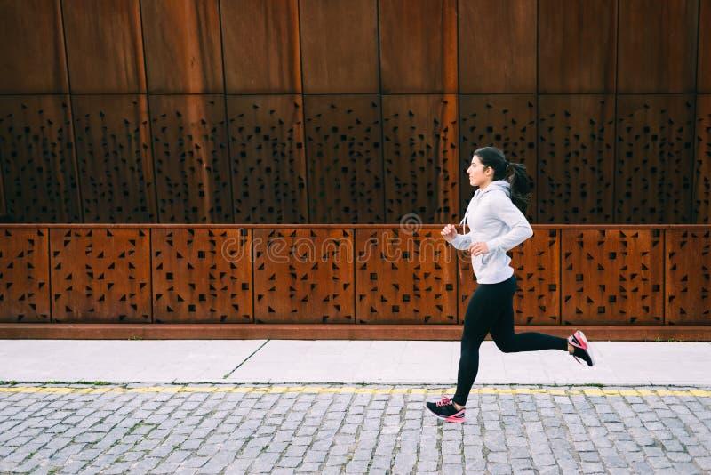 Funcionamiento urbano del atleta de sexo femenino al aire libre imagen de archivo