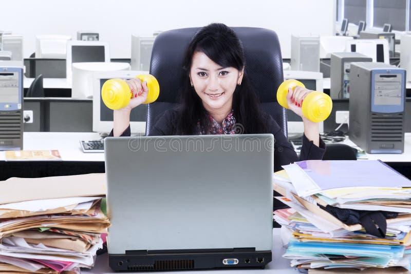 Funcionamiento y entrenamiento de la mujer en oficina imagen de archivo