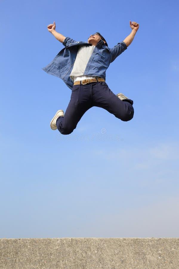 Funcionamiento y salto felices del hombre foto de archivo