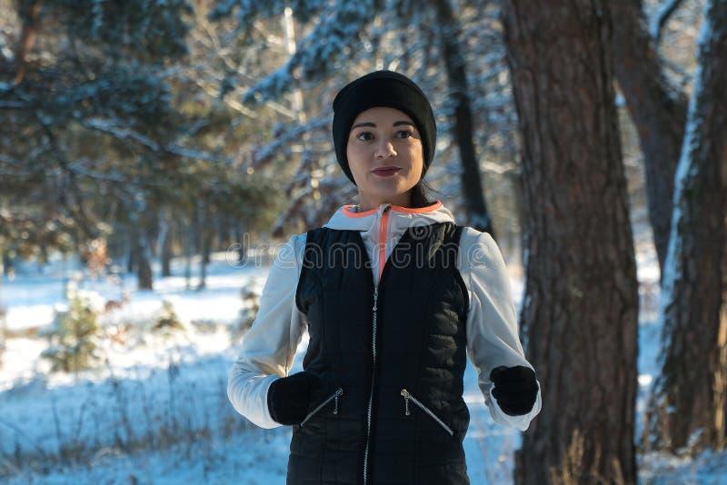 Funcionamientos de funcionamiento de funcionamiento de la muchacha de la nieve del invierno a través del bosque en invierno del d imagen de archivo