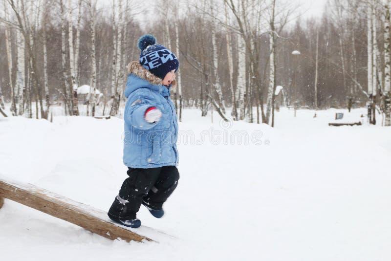 Funcionamientos del niño pequeño en parque del inicio de sesión durante las nevadas imagenes de archivo