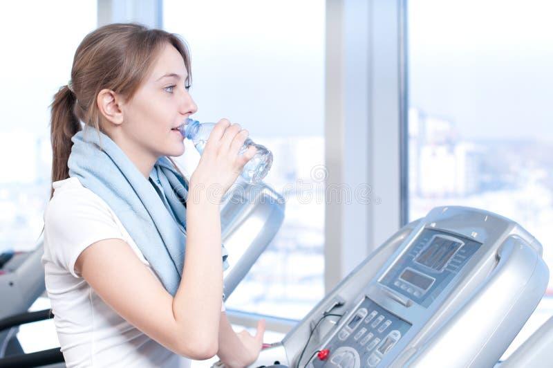 Funcione sobre em uma máquina e beba a água foto de stock